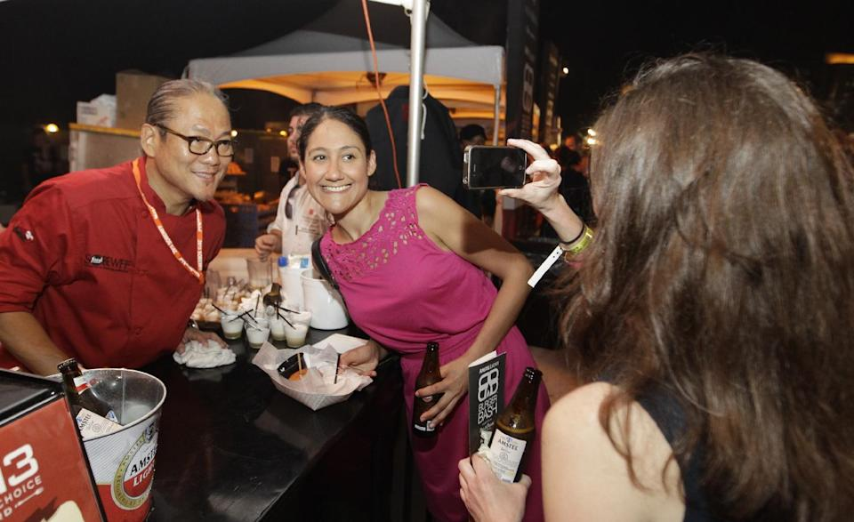 Iron Chef Masaharu Morimoto, left, poses for a picture with Joy Jamir, center, at the South Beach Wine and Food Festival's Burger Bash, Friday, Feb. 22, 2013, in Miami Beach, Fla. (AP Photo/Luis M. Alvarez)
