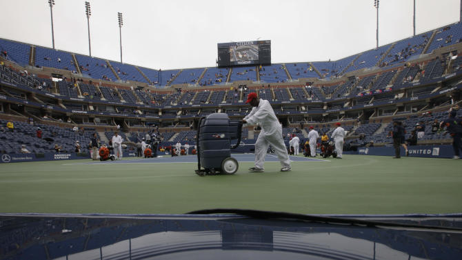 Workers clear water from the court at Arthur Ashe Stadium during a rain delay at the U.S. Open tennis tournament in New York, Wednesday, Sept. 7, 2011. (AP Photo/Matt Slocum)