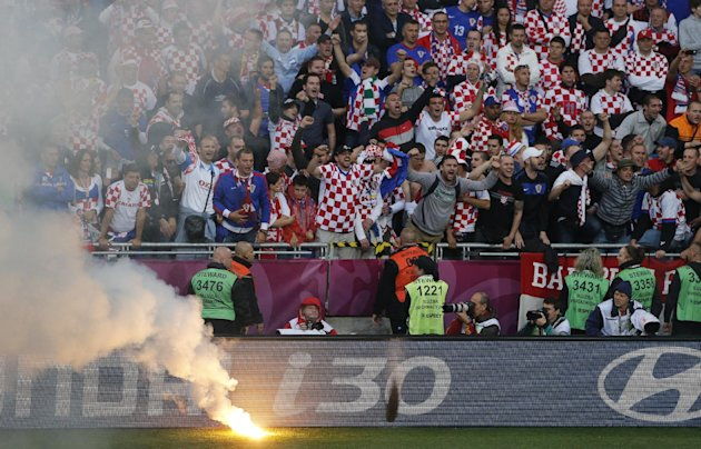 FILE - The June 14, 2012 file photo shows Croatian fans cheering after a flare was thrown onto the pitch during the Euro 2012 soccer championship Group C match between Italy and Croatia in Poznan, Pol