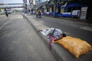 A homeless man sleeps on a kerb during a nationwide strike in Dhaka on Sunday. Seven small bombs exploded in the Bangladeshi capital Dhaka on Sunday, police said, after an opposition supporter was shot dead in clashes ahead of a fourth nationwide strike in eight days