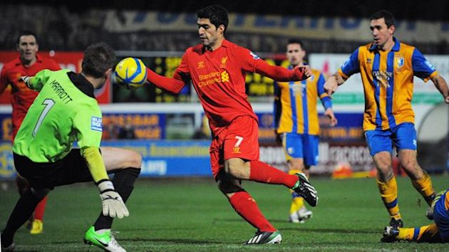 Liverpool's Uruguayan forward Luis Suarez (C) appears to handle the ball in the lead up to his goal during the FA Cup third round football match between Mansfield Town and Liverpool at Field Mill (AFP)