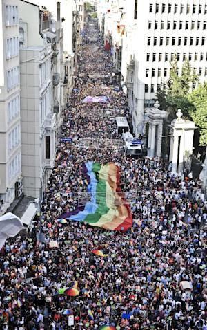 People hold a giant rainbow flag during a gay pride…