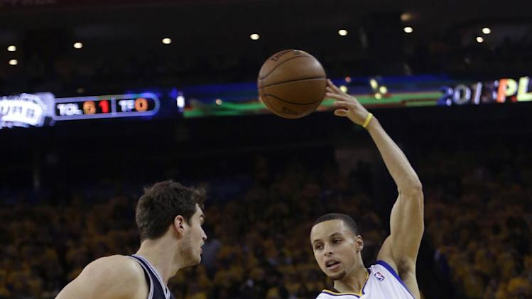 Golden State Warriors guard Stephen Curry (30) passes over San Antonio Spurs center Tiago Splitter (22) in the first quarter of Game 6 of a Western Conference semifinal NBA basketball playoff series in Oakland, Calif., Thursday, May 16, 2013. (AP Photo/Marcio Jose Sanchez)