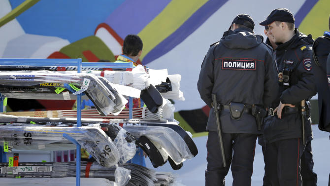 FILE - In this Feb. 10, 2014 file photo, police officers look over a cart of hockey sticks after they were taken off a plane as NHL hockey players arrive at the Sochi International Airport for the 2014 Winter Olympics, in Sochi, Russia.Sochi hotel guests are walking, unchecked, past unused metal detectors. Security guards are no longer poking around at the pockets and ankles of every single person entering Olympic facilities. Tangerines and bottles of Coke are making it through security barriers that banned them two weeks ago. For all the warnings that security in Sochi would be invasive and aggressive, it's appearing more uneven, and in places almost relaxed. (AP Photo/Mark Humphrey, File)