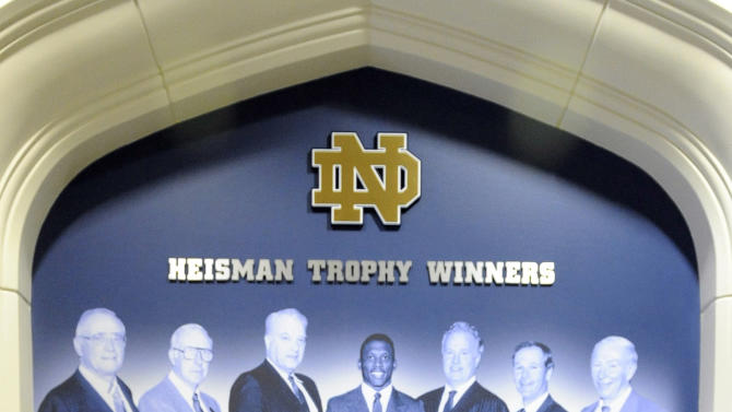 In this Dec. 27, 2012, photo, a Heisman Trophy is displayed in front of a mural showing seven winners from Notre Dame in the lobby of the Guglielmino Athletics Complex on the campus of the University of Notre Dame in South Bend, Ind. (AP Photo/Joe Raymond)