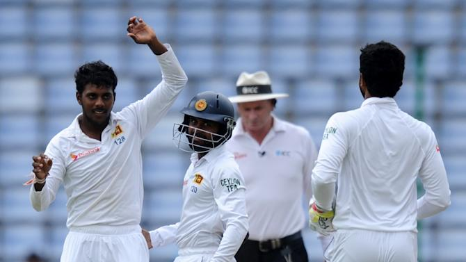 Sri Lanka's Tharindu Kaushal (L) celebrates with his teammates Kaushal Silva (C) and Dinesh Chandimal (R) after he dismissed Pakistan's Imran Khan during the third day  of the third and final Test in Pallekele on July 5, 2015
