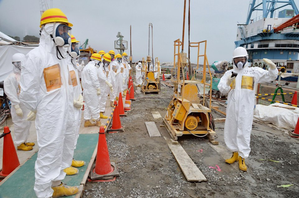 In this Aug. 6, 2013 photo, officials and experts from local towns inspect a coastal embankment where contaminated water leaks occur near Fukushima Dai-ichi nuclear plant Unit 1 and 2 of Tokyo Electric Power Co., in Okuma, Fukushima prefecture, northeastern Japan. Japan's government said Wednesday, Aug. 7, 2013, it will step in to tackle contaminated water leaks at the country's crippled nuclear plant, and is considering funding a multibillion-dollar project to fix the problem. (AP Photo/Kyodo News) JAPAN OUT, MANDATORY CREDIT