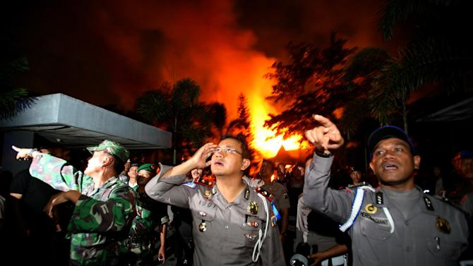 Police officers and soldiers give orders to others as they are deployed outside Tanjung Gusta prison that was partially set ablaze by inmates during a prison riot in Medan, North Sumatra, Indonesia, Thursday, July 11, 2013. About 150 prisoners have reportedly escaped from the overcrowded prison in western Indonesia following a riot triggered by a power outage. (AP Photo/Binsar Bakkara)