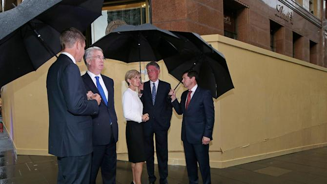 British Foreign Secretary Philip Hammond, second right, and Michael Fallon, Secretary of State for Defence, second left, visit the boarded Lindt Cafe with Australian Foreign Minister Julie Bishop, center, Australia's Minister for Defence Kevin Andrews, right, and New South Wales state Premier Mike Baird, left, before Australia-UK Ministerial meetings (AUKMIN) in Sydney, Monday, Feb. 2, 2015.  The cafe was the scene of a siege where three people, including the lone gunman, died in Dec. 2014. (AP Photo/Rick Rycroft)