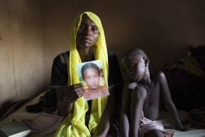 File photo shows Daniel holding up a picture of her abducted daughter as her son sits beside her at her home in Maiduguri