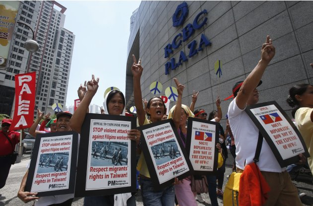 Filipino activists and overseas Filipino workers gesture as they chant slogans during a rally outside the premises of the Taipei Economic and Cultural Office (TECO), in Manila's Makati financial distr