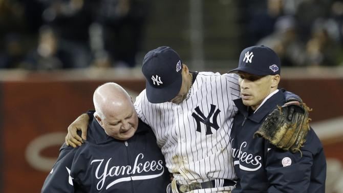 Trainer Steve Donohue, left, and New York Yankees manager Joe Girardi, right, help Yankees' Derek Jeter off the field after he injured himself during Game 1 of the American League championship series against the Detroit Tigers Sunday, Oct. 14, 2012, in New York.(AP Photo/Paul Sancya )