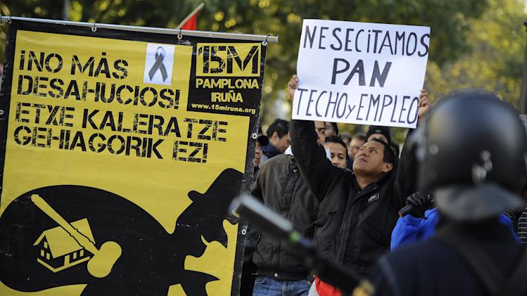 A man who identified himself as Edwin, 32, from Ecuador, right, who was evicted from his home over debts,  holds up banner reading ''We need bread, roof and employment''  beside a poster to support people fighting against evictions reading, ''No More Evictions'', in front of Spanish riot police during a general strike against government austerity measures, in Pamplona, northern Spain, Wednesday, Nov. 14, 2012.  A Spanish Interior Ministry official says 32 people have been arrested and 15 people treated for minor injuries in disturbances as a general strike in Spain against austerity measures and economic reforms began. The General Workers Union said the nationwide stoppage, the second this year, was being heeded by nearly 100 percent of workers Wednesday in the automobile, energy, shipbuilding and constructions industries. (AP Photo/Alvaro Barrientos)