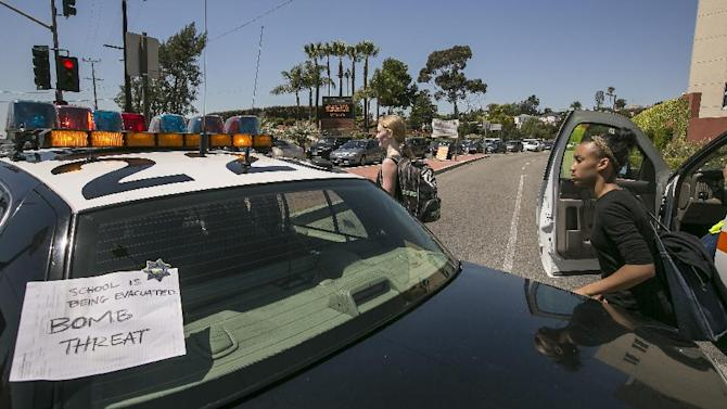 A sign is posted on a police car to inform students of a bomb threat the Cal State University Los Angeles campus, after a mandatory evacuation on a report of a suspicious item, according to the Los Angeles Police Department in Los Angeles Thursday, April 18, 2013. Two telephoned bomb threats prompted officials at Cal State Los Angeles today to cancel afternoon classes and evacuate the campus. (AP Photo/Damian Dovarganes)