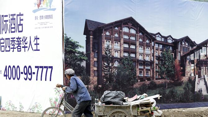 Villager pushes a tricycle past a billboard of local real estate advertisement in Chongli county of Zhangjiakou