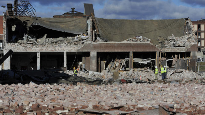 Inspectors assess damage, Saturday, Nov. 24, 2012, around the area of a gas explosion that leveled a strip club in Springfield, Mass., on Friday evening. Investigators were trying to figure out what caused the blast where the multistory brick building housing Scores Gentleman's Club once stood. (AP Photo/Jessica Hill)