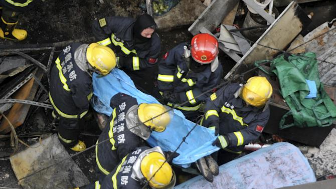 Firefighters put the body of a victim on a stretcher after an explosion at a restaurant in Wuhu