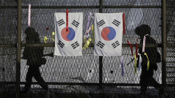 FILE - In this Wednesday, Feb. 13, 2013 file photo, South Korean army soldiers patrol by the national flags and ribbons, wishing for the reunification of the two Koreas, attached on the barbed-wire fence at the Imjingak Pavilion near the border village of Panmunjom, which has separated the two Koreas since the Korean War, in Paju, north of Seoul, South Korea. Separated from the North by a heavily fortified border since the 1953 Korean War armistice, they have for the most part lived with tough talk from Pyongyang all their lives. In annual drills, war alarms literally ring in their ears. (AP Photo/Lee Jin-man)