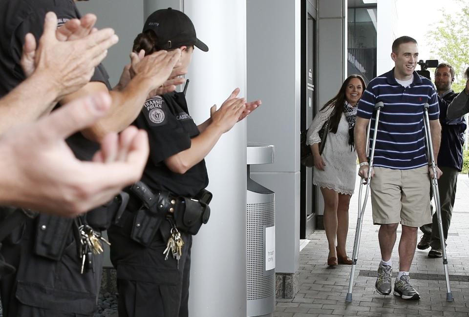 Transit police officer Richard Donohue, front right, leaves Spaulding Rehabilitation Hospital in Boston, followed by his wife Kim, center, Friday, June 14, 2013. Donohue was injured during a shoot-out with the Boston Marathon bombing suspects. (AP Photo/Michael Dwyer)