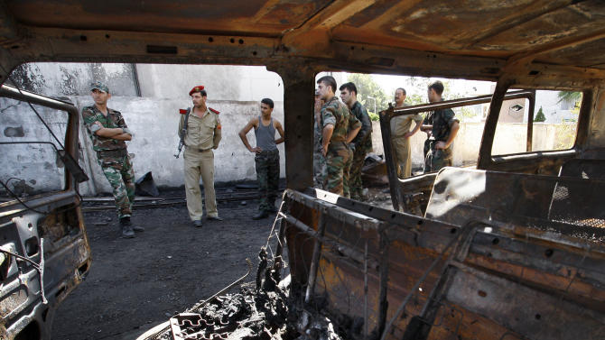 Syrian soldiers investigate the scene after a bomb attached to a fuel truck exploded outside a Damascus hotel where U.N. observers are staying in Damascus, Syria, Wednesday, Aug. 15, 2012. Several  people were wounded, Syria's state TV reported. TV said the explosion took place near a parking lot used by the army command, which is about 300 meters (yards) away. (AP Photo/Muzaffar Salman)