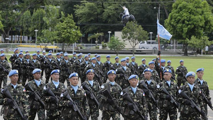 In this Friday, July 18, 2014 photo, a contingent of Philippine U.N. Peacekeepers march past the grandstand during a turnover-of-command ceremony for the new Armed Forces chief at Camp Aguinaldo at suburban Quezon city, northeast of Manila, Philippines. Forty-four Fijian soldiers working as U.N. peacekeepers remained captive to a militant group in Syria Friday, Aug. 29, 2014 while 75 Philippine soldiers were in tense standoff with the rebels, according to the two Pacific nations. Both nations remained hopeful the impasse could be resolved without bloodshed. Philippines President Benigno Aquino III said that while the situation remained tense, there was no reason to believe his troops faced immediate danger. (AP Photo/Bullit Marquez)