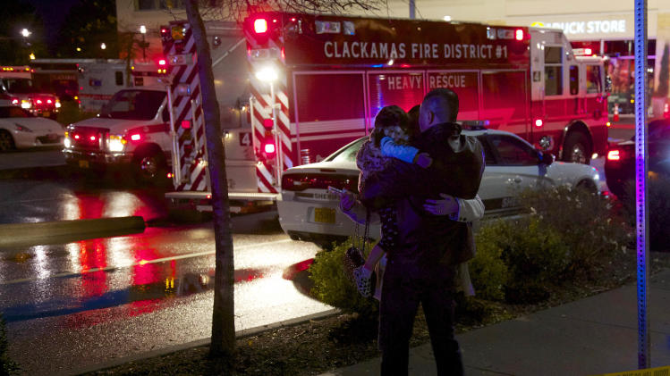 A couple with a child embrace after they were released from the mall at Clackamas Town Center in Portland, Ore., Tuesday, Dec. 11, 2012. Witnesses say the scene went from cheery to chaotic in seconds when a gunman opened fire in the suburban Portland shopping mall Tuesday, killing two people and wounding another. (AP Photo/The Oregonian, Thomas Boyd)  MAGS OUT; TV OUT; LOCAL TV OUT; LOCAL INTERNET OUT; THE MERCURY OUT; WILLAMETTE WEEK OUT; PAMPLIN MEDIA GROUP OUT