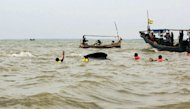 Tourist boats surround rescuers trying to free a sperm whale (C) stuck in shallow waters at Pakis Jaya beach in Karawang, West Java, July 27, 2012. Local residents were paying the equivalent of half a US dollar each for boat rides close to the whale. Some had jumped off the boats and onto the whale on Wednesday, causing wounds to its body