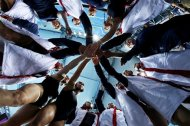 In this photo taken with a fisheye lens, Britain women&#39;s water polo players huddle before the seventh place water polo match at the 2012 Summer Olympics, Thursday, Aug. 9, 2012, in London. (AP Photo/Julio Cortez)