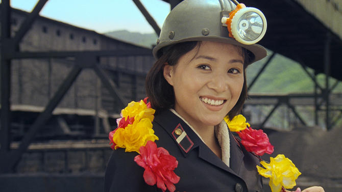 "In this image made out of film ""Comrade Kim Goes Flying"" released on Wednesday, Oct. 3, 2012 by Busan International Film Festival, Comrade Kim Yong Mi played by Han Jong Sim smiles as she wears a coal miner's helmet. Along with the now inevitable galaxy of stars promoting blockbusters from across Asia, this year's Busan International Film Festival will screen the North Korean film for the first time in almost a decade as well as six classic Afghan movies that were hidden in a wall to save them from a radical Taliban regime that banned most entertainment. (AP Photo/Busan International Film Festival)"