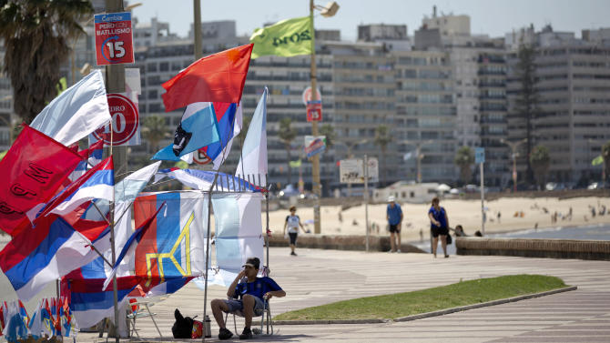 A man sells political party flags ahead of elections near the beach in Montevideo, Uruguay, Saturday, Oct. 25, 2014. The political party of outgoing President Jose Mujica, who gained international renown for social reforms such as legalization of marijuana and gay marriage, leads going into Sunday's election to replace him but is far from assured a resounding win. (AP Photo/Natacha Pisarenko)
