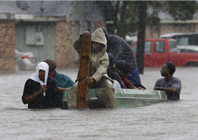 FILE - In this Aug. 30, 2012 file photo, residents evacuate their flooded neighborhood in LaPlace, La. as Hurricane Isaac staggered toward central Louisiana, its weakening winds driving storm surge in