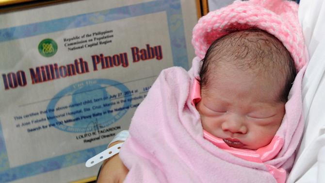 """Newly-born baby girl Jennalyn Sentino, the Philippines' """"100,000,000th baby"""", sleeps in her mother's arms during a presentation at a government hospital in Manila on July 27, 2014"""