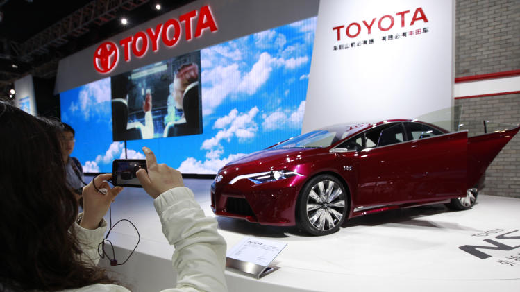 FILE - In this April 24, 2012 file photo, a visitor takes pictures of the Toyota NX4 concept car during the Beijing International Automotive Exhibition in Beijing, China. Japan's top automaker said Friday, May 25, 2012, it is looking to emerging markets for growth, targeting 50 percent of its global vehicle sales there by 2015, and rolling out eight compact models over the next few years. (AP Photo/Vincent Thian, File)