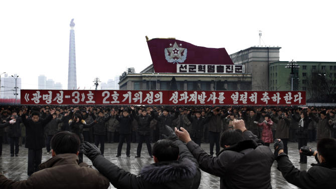 "North Koreans dance near a slogan which reads ""(we) fervently celebrate the successful launch of the second version of the Kwangmyongsong-3 satellite"" during a mass rally organized to celebrate the success of a rocket launch that sent a satellite into space, on Kim Il Sung Square in Pyongyang, North Korea, Friday, Dec. 14, 2012. As the U.S. led international condemnation of what it calls a covert test of missile technology, top North Korean officials denied the allegations and maintained the country's right to develop its space program. (AP Photo/Jon Chol Jin)"