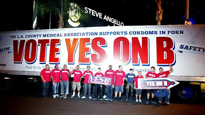 Supporters of Vote Yes on B in Los Angeles, the condoms in porn measure on the November ballot led by AIDS Healthcare Foundation, hand out voter information and free condoms on L.A's famed Sunset Strip on Saturday, Oct. 27, 2012, in Los Angeles, Calif.  After an all day caravan to five cities throughout Los Angeles. The 'Yes on B' caravan covered 137 miles through Hollywood, Long Beach, Northridge, Canoga Park and West Hollywood handing out 150,000 condoms with only ten days before election day. (Photo by Joe Kohen/AP Images for AIDS Healthcare Foundation)