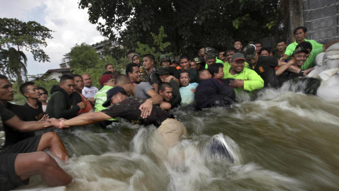 Thai soldiers hold onto each other against the stream of water flowing into a neighborhood after a wall was breached by the swollen Chao Phraya River in Bangkok, Thailand, Sunday, Oct. 30, 2011. (AP Photo/Altaf Qadri)