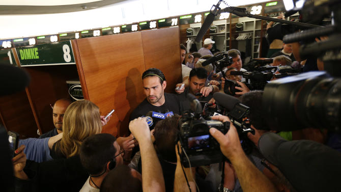 New York Jets quarterback Mark Sanchez, center, talks to reporters during a locker room availability at the team's NFL practice practice facility in Florham Park, N.J., Thursday, May 2, 2013. The Jets may have cut Tim Tebow but their situation at quarterback is far from settled. New general manager John Idzik says Sanchez, David Garrard, Greg McElroy, Matt Simms and second-round draft pick Geno Smith are all candidates to be the starter. (AP Photo/Rich Schultz)