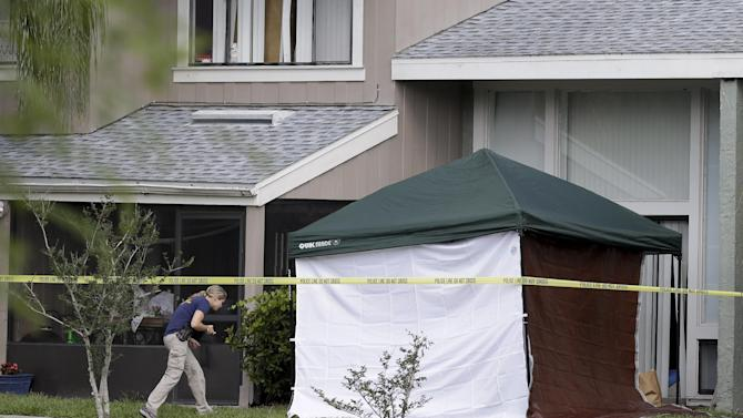 An FBI investigator walks to the apartment where a man was shot by an FBI agent, Wednesday, May 22, 2013, in Orlando, Fla. The FBI says the man, being questioned by authorities in the Boston bombing probe, was fatally shot when he initiated a violent confrontation. (AP Photo/John Raoux)