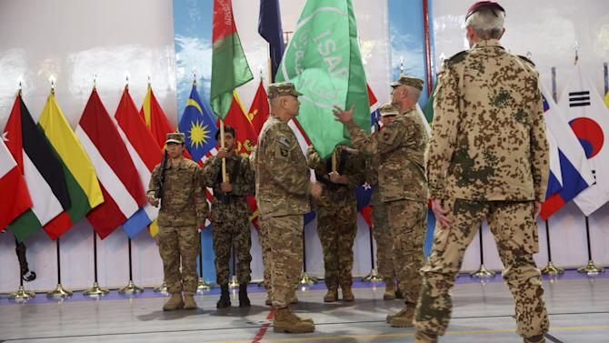 Commander of the International Security Assistance Force (ISAF), Gen. John Campbell, center, and Command Sgt. Maj. Delbert Byers, center right, case the ISAF flag during a ceremony at the ISAF headquarters in Kabul, Afghanistan, Sunday, Dec. 28, 2014. The United States and NATO formally ended their war in Afghanistan on Sunday with the ceremony at their military headquarters in Kabul as the insurgency they fought for 13 years remains as ferocious and deadly as at any time since the 2001 invasion that unseated the Taliban regime following the Sept. 11 attacks. (AP Photo/Massoud Hossaini)
