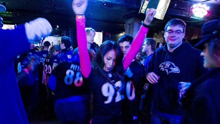 Baltimore Ravens fans celebrate after their team scored the third touchdown against the San Francisco 49ers, during the Super Bowl at local pub in Baltimore on Sunday Feb. 3, 2013. (AP Photo/Jose Luis Magana)