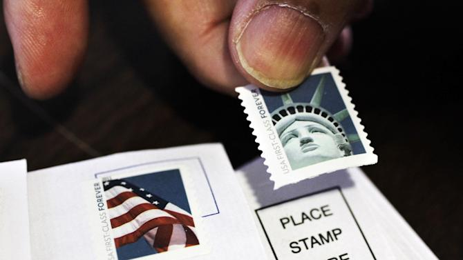 FILE - In this Dec. 5, 2011, photo, a customer places first class stamps on envelopes at a U.S. Post Office in San Jose, Calif. It'll cost another penny to mail a letter in 2013. The cash-strapped U.S. Postal Service said Thursday that it will raise postage rates on Jan. 27, including a 1-cent increase in the cost of first-class mail to 46 cents. (AP Photo/Paul Sakuma, File)