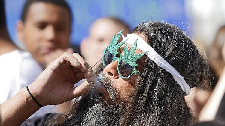 A man smokes a joint as thousands gather to celebrate the state's medicinal marijuana laws and collectively light up in Civic Center Park April 20, 2012 in Denver, Colorado
