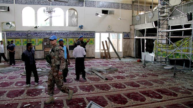 FILE - In this June 14, 2012, file photo, UN observers inspect the prayer hall of the Sayyida Zeinab shrine which was damaged after a car bomb exploded near the shrine, in a suburb of  Damascus, Syria. Iraqi Shiites increasingly fear the Muslim sect and its holy sites could be targeted in Syria, and Iranian-linked militants loyal to the faction are girding for a new eruption of retaliatory sectarian fighting, according to Iraqi Shiite leaders and government officials. (AP Photo/Bassem Tellawi, File)