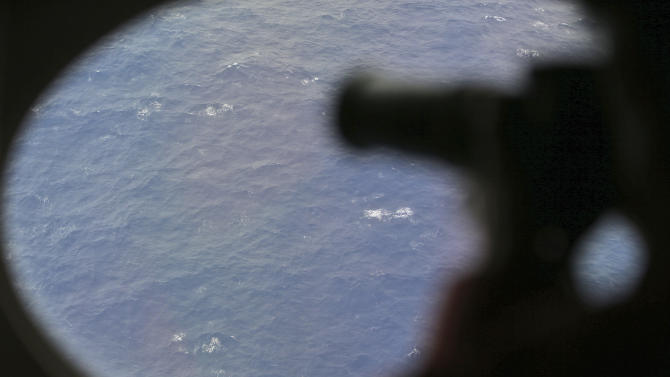 """FILE - In this April 1, 2014 file photo, an observer on a Japan Coast Guard Gulfstream aircraft takes photos out of a window while searching for the missing Malaysia Airlines Flight 370 in Southern Indian Ocean. In an interview with The Associated Press, Martin Dolan, chief commissioner of the Australian Transport Safety Bureau, said that he was """"cautiously optimistic"""" that the lost jet would be found. Dolan said he was confident the airliner was close to a 700-kilometer by 80-kilometer (430 mile by 50 mile) arc of ocean identified from satellite data that investigators would be scouring in the next phase of the search. (AP Photo/Rob Griffith, Pool, File)"""