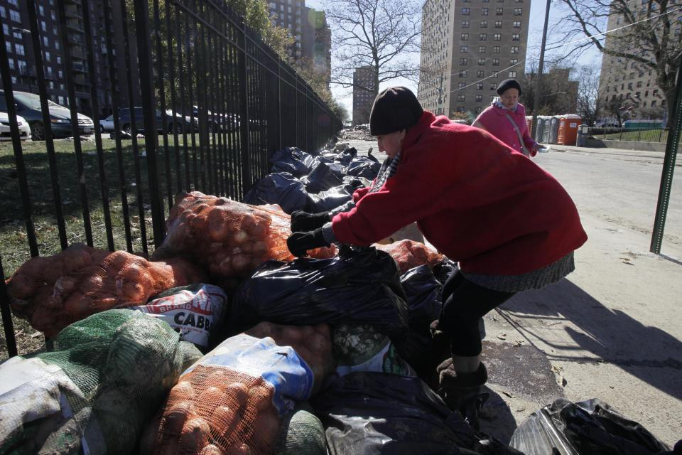 A woman scavenges a sack of onions discarded by a Coney Island supermarket in the Brooklyn borough of New York, Sunday, Nov. 4, 2012 in New York. Many people in Coney Island are still living without heat, and some without electricity, six days after Sandy struck the region. (AP Photo/Mark Lennihan)