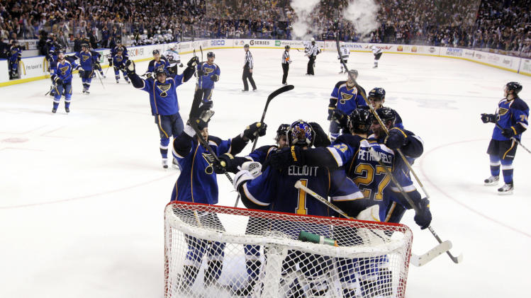 St. Louis Blues players celebrate with goaltender Brian Elliott as time expires against the San Jose Sharks during the third period in Game 5 of an NHL Stanley Cup first-round hockey playoff series, Saturday, April 21, 2012, in St. Louis. The Blues won 3-1 and won the series 4-1. (AP Photo/St. Louis Post-Dispatch, Chris Lee)  EDWARDSVILLE INTELLIGENCER OUT; THE ALTON TELEGRAPH OUT