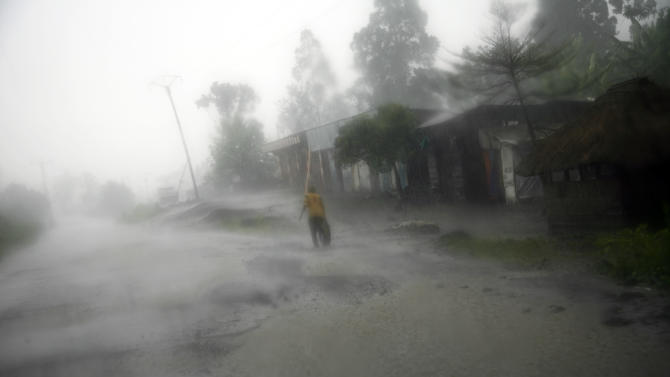 A  lone man walks in a rain storm in Goma, eastern Congo, Friday Nov. 23 2012.  Thousands fled the M23 controlled town  as   platoons of rebels were making their way across the hills from Sake to the next major town of Minova, where the Congolese army was believed to be regrouping. The militants seeking to overthrow the government vowed to push forward despite mounting international pressure.(AP Photo/Jerome Delay)