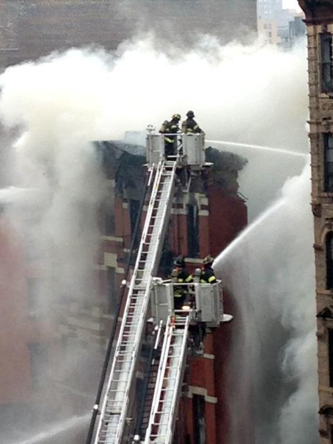 New York City firefighters spray water at scene of a large fire and building collapse in New York on Thursday, March 26, 2015. An apartment building collapsed and flames spread to two nearby buildings. (AP Photo/Tom Hays)