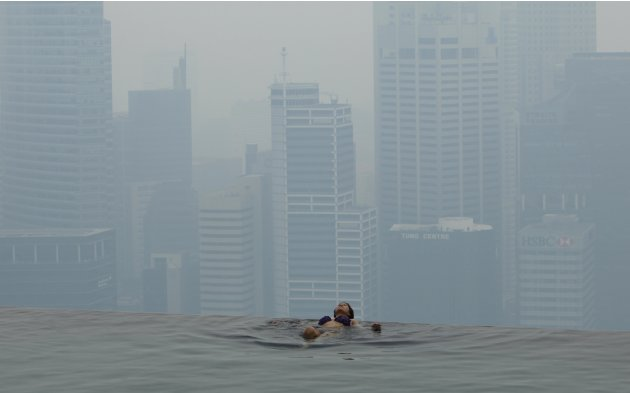 Hotel guest rests in the pool of the Marina Bay Sands Skypark in front of the hazy skyline of Singapore