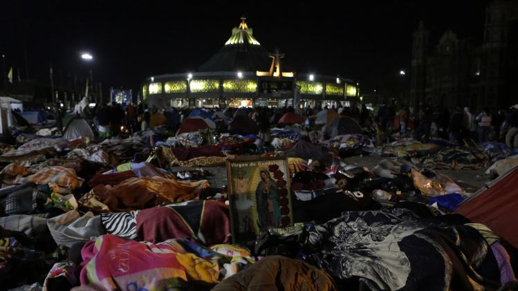Pilgrims sleep next to an image of the Virgin of Guadalupe inside the Basilica of Guadalupe during the annual pilgrimage in Mexico City